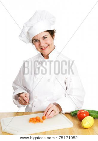 Petty female chef in her uniform, cutting up a variety of fresh organic vegetables on her cutting board in the kitchen.  Isolated on white background.