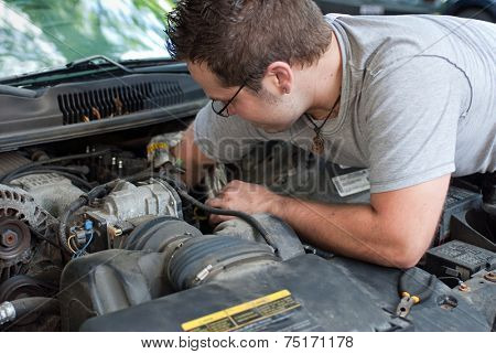 Young Mechanic Working on Car Engine