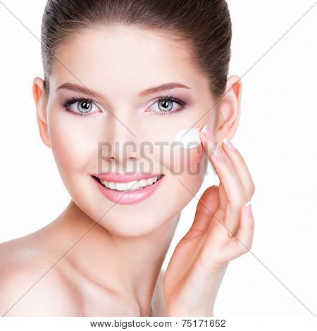 Beauty face of young woman with cosmetic cream on a cheek. Skin care concept. Closeup portrait isolated on white.