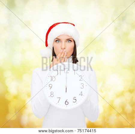 christmas, time, winter and people concept - smiling woman in santa helper hat with clock showing 12 over yellow lights background