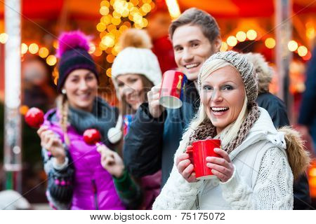 Friends drinking mulled wine and eating crystalized appkes on German Christmas Market