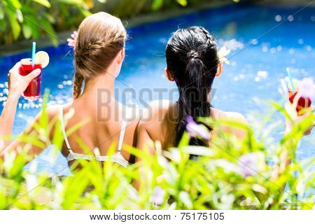 Two girls or women in vacation, Asian and Caucasian, in tropical garden bathing in hotel pool with drinks or cocktails