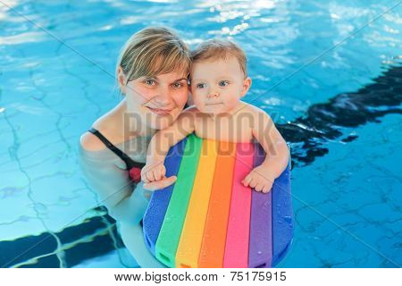 Little Baby Boy And His Mother Learning To Swim In An Indoor Swimming Pool