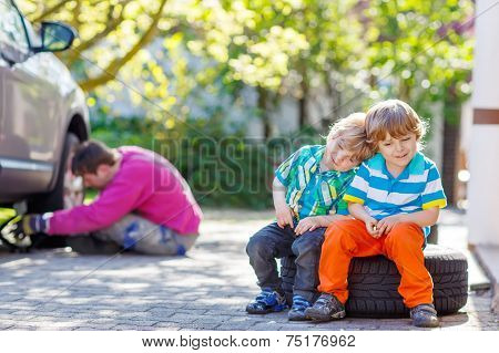 Father And Two Little  Kid Boys Repairing Car And Changing Wheel Together