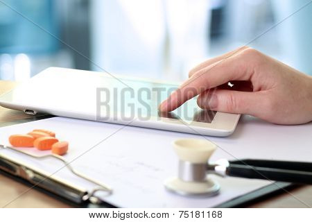 Doctor  Working With Tablet Computer. Orange Pills,  Prescription And Phonendoscope Behind