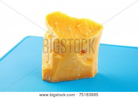 piece of solid gouda cheese on blue board