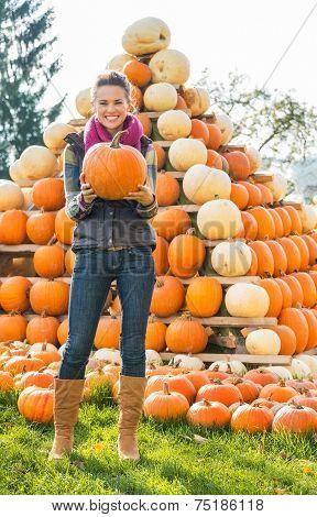 Portrait Of Happy Young Woman Holding Pumpkin In Front Of Pumpkin Piramide