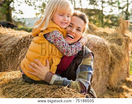 Portrait Of Happy Mother And Child Hugging While On Haystack