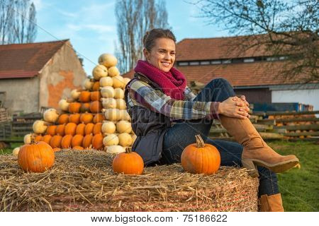 Portrait Of Young Woman Sitting On Haystack With Pumpkin In Fron