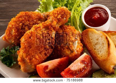Fried chicken drumsticks and vegetables