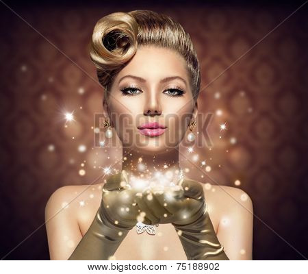 Holiday Retro Woman blowing magic dust in her hand. Beauty Fashion Christmas Vintage Style Lady with Beautiful Luxury Hairstyle, makeup, accessories. Golden Silk Gloves and dress