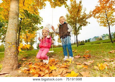Girl sitting on swings and blond boy standing near