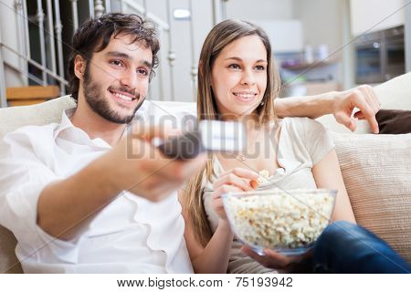 Couple using a remote control while sitting on the couch