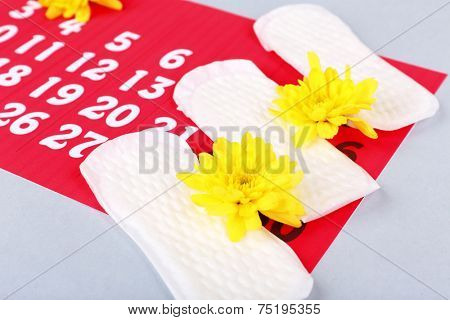 Sanitary pads and yellow flowers on light grey background