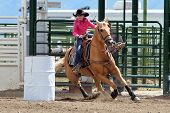 stock photo of barrel racing  - Beautiful young cowgirl riding a palomino horse in a barrel race - JPG