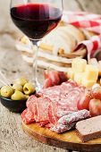 pic of charcuterie  - Glass of red wine with charcuterie assortment on the background - JPG