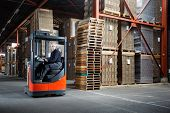 foto of forklift driver  - Reach truck driver in a warehouse where pallets and cardboards are stored - JPG
