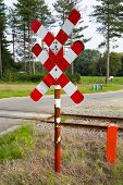 pic of railroad-sign  - Red and white railroad crossing sign and road - JPG