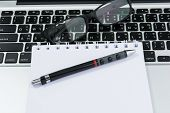 stock photo of field mouse  - Blank business laptop mouse pen and glasses on white table  - JPG