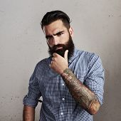 picture of hooligan  - Portrait of thoughtful bearded man with tattoo on concrete wall background - JPG