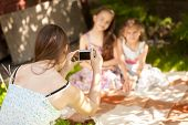 stock photo of little girls photo-models  - Young beautiful mother making photo of daughters on picnic - JPG
