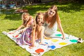 picture of daycare  - Happy mother and girls having fun with twister on grass at park - JPG