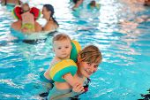 stock photo of swimming  - Little baby boy and his mother learning to swim in an indoor swimming pool - JPG