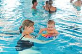 pic of swimming  - Little baby boy and his mother learning to swim in an indoor swimming pool - JPG