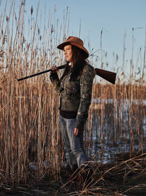 picture of shotgun  - Waterfowl hunting female hunter carry a shotgun reeds and blue sky on background  - JPG