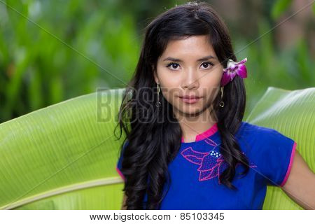 Pretty serious young Vietnamese woman with a fresh orchid flower in her long hair standing looking at the camera in front of a banana tree leaf
