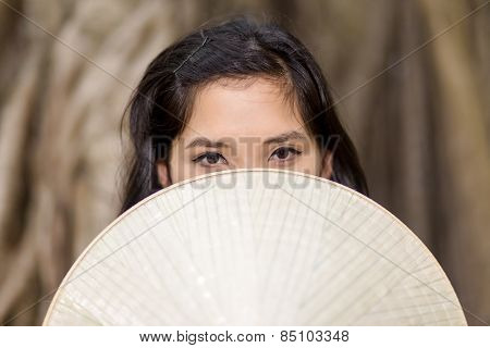 Close up Mysterious Young Woman Covering her Half Face with conical hat While Looking at the Camera.