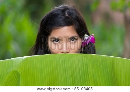 Sensual portrait of a young Vietnamese woman peeking over the top of a banana tree leaf at the camera with a purple orchid flower in her hair