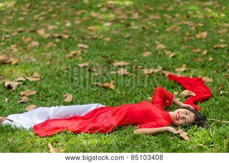 Happy Young Pretty Asian Woman in Red and White Dress Lying Down on Grassland While Looking at the Camera.