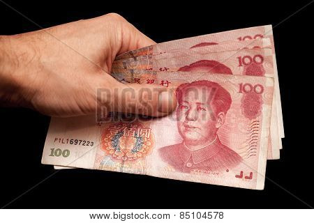 Chinese Banknotes In Male Hand Isolated On Black