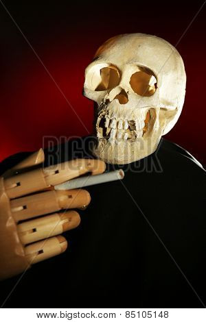 Human scull and wooden hand with cigarette on dark color background