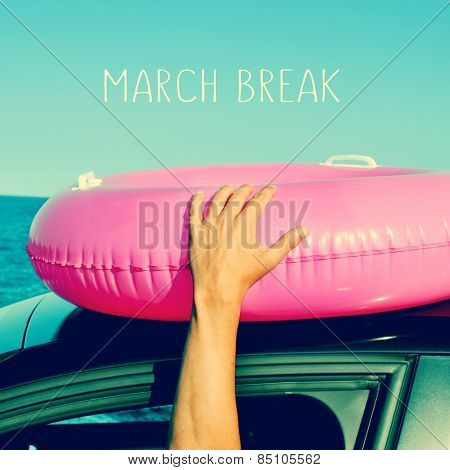 a young man holding a pink swim ring in the roof of a car near the ocean and the text march break written in the blue sky