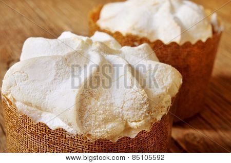 some merengues, meringue baked in paper cups typical of Spain, on a wooden table
