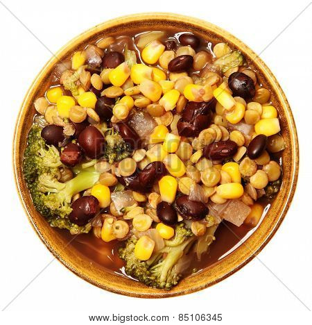 Vegan lentil soup and veggies in bowl with black beans, broccoli, onion, corn over white. Top view.