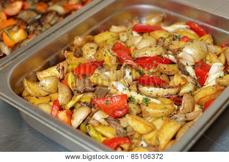 Steel container with potato wedges and vegetables