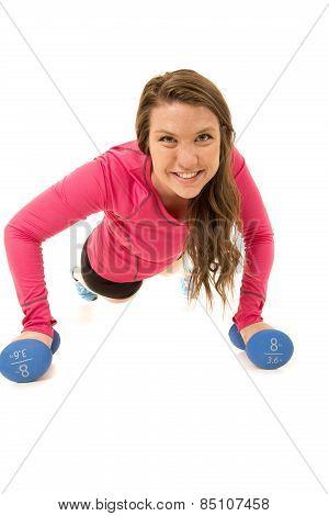 Woman Doing Pushups On Barbells Looking At Camera Smiling