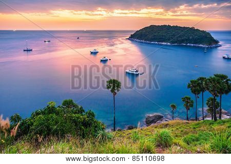 Panoramic view on sunset sea, small island, palms and boats in fish-eye lense. Nature background