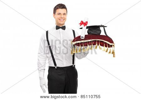 Male butler holding a diploma and a mortarboard on a red pillow isolated on white background