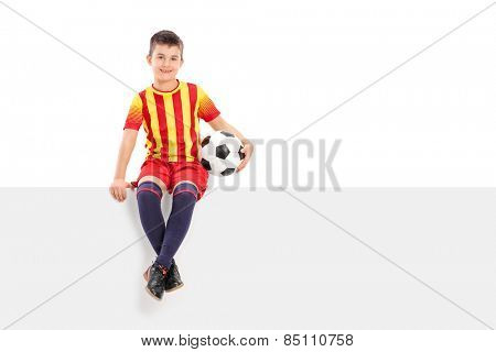 Junior soccer player sitting on a signboard isolated on white background