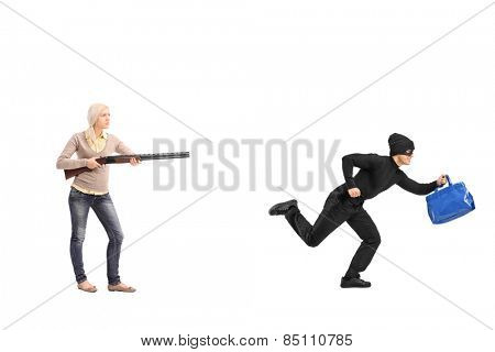Full length portrait of an angry woman chasing a burglar with a shotgun isolated on white background