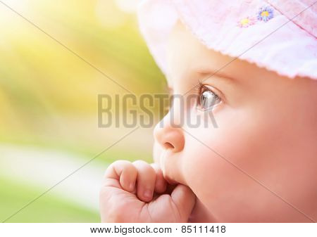 Closeup portrait of a sweet little baby girl in bright light of sunny day, cute kid face over blur green background, child enjoying outdoors, innocence and happiness