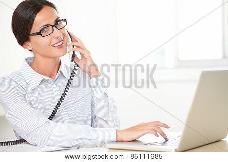 Hispanic Female Employee Conversing On The Phone