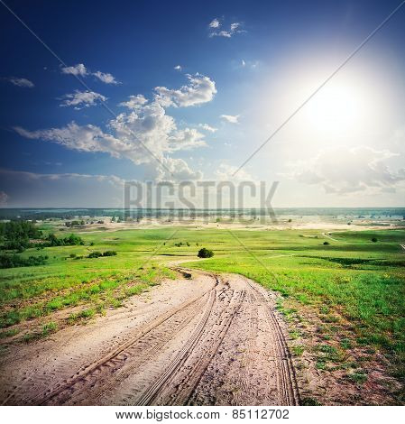 Sandy dirt road in a green field