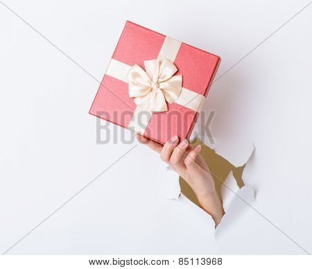 Hand hold with gift box through the white paper