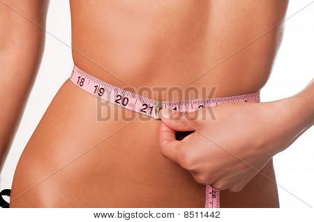 Slim young woman measuring waist.