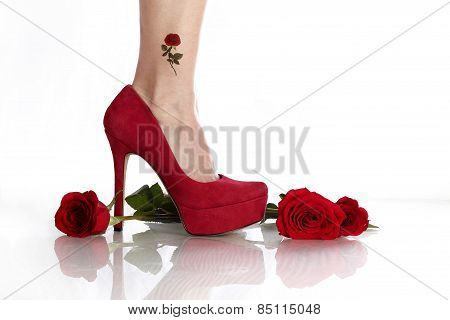 Red roses and red stiletto on a reflective surface